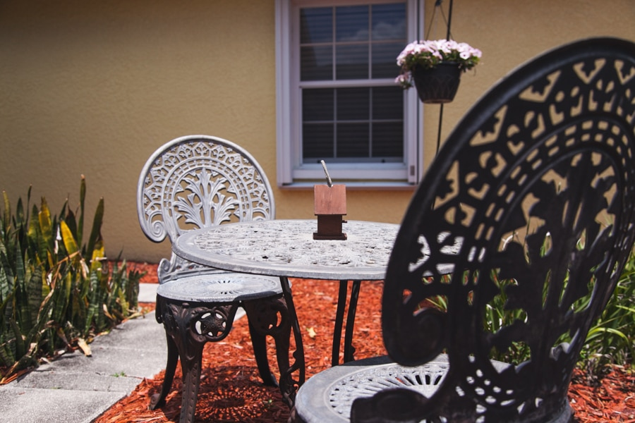 Close-up of black iron wrought table with two black iron wrought chairs and a bird box as a centerpiece.