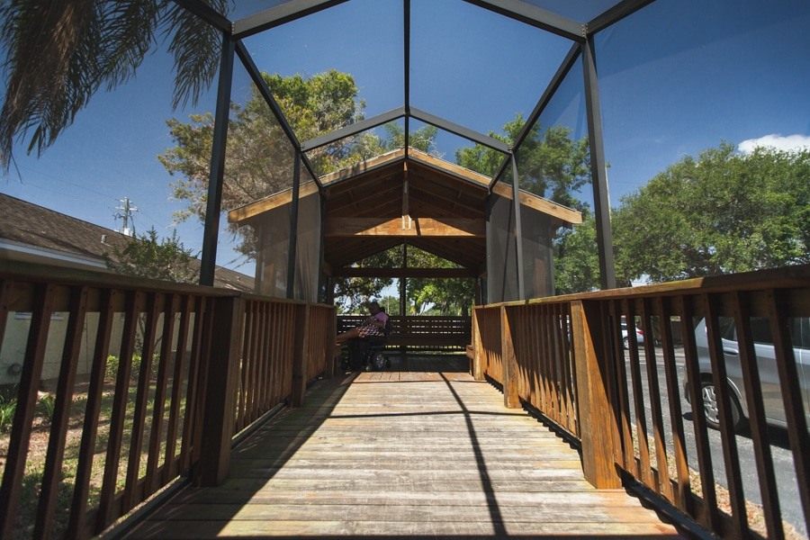 Screened-in wooden walkway leading to covered wooden porch where residents can relax.