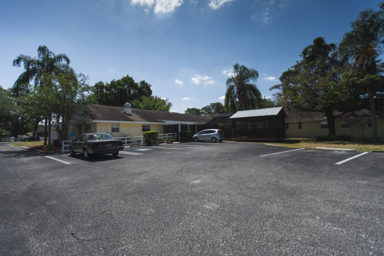 Parking lot with two cars in it with North Tampa assisted living facility and fenced-in patio in the background.