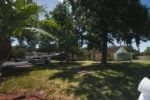 Far-off look at North Tampa ALF, including oak trees, front of building, and parking lot.