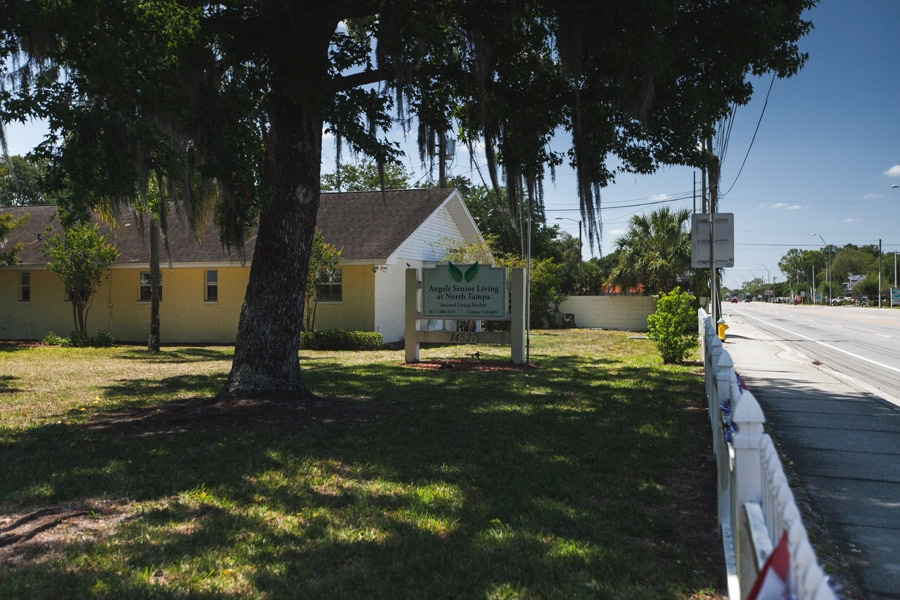 Exterior of our assisted living facility in North Tampa including sign with phone number and license number, large oak tree, and one wing of property.