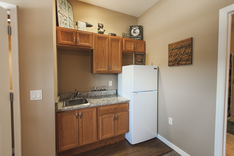 Fishing-inspired kitchenette with brown cabinet doors and white refrigerator, plus granite countertop.