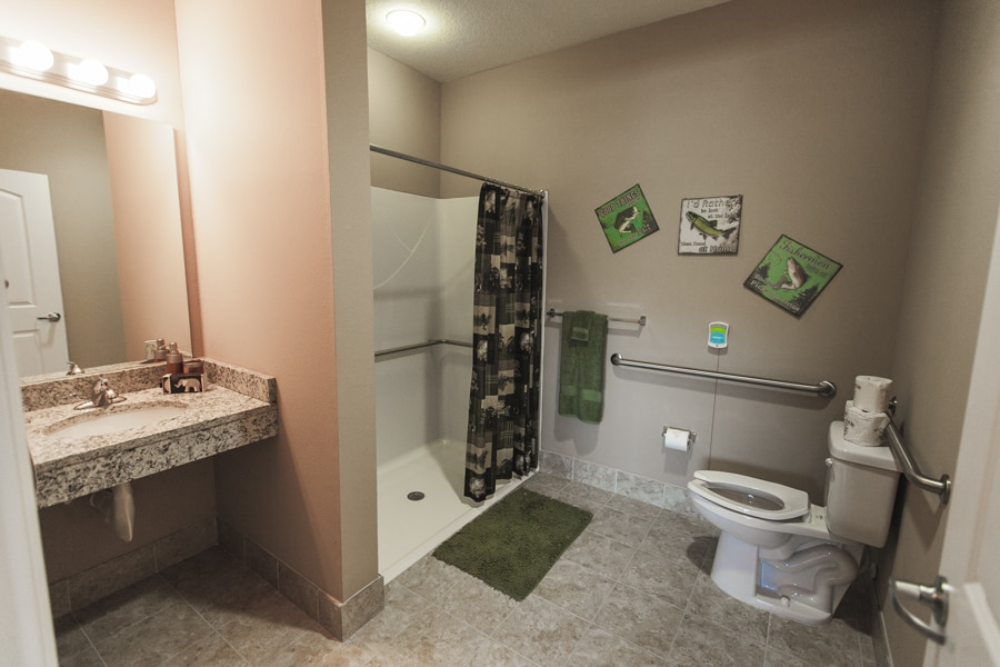 Tiled modern bathroom with curbless entry for seniors, granite vanity, porcelain toilet, and fisherman-inspired decorations.