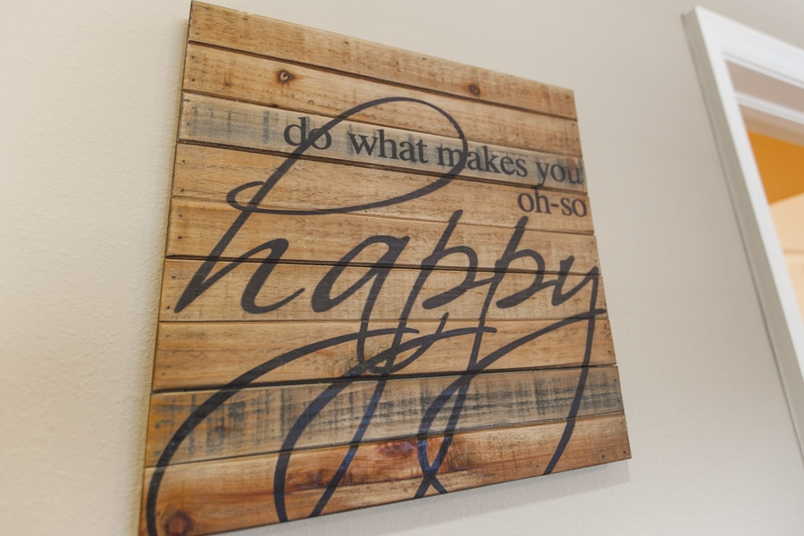 """Wooden plaque with black script reading """"do what makes you oh-so happy"""" attached to a white wall."""