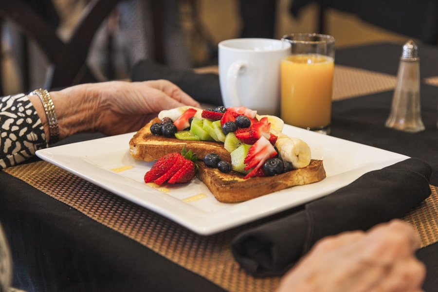 A white plate with assorted fruit atop two pieces of toast, with orange juice in the background.