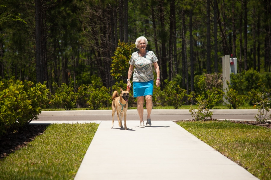 woman in assisted living facility and dog walking