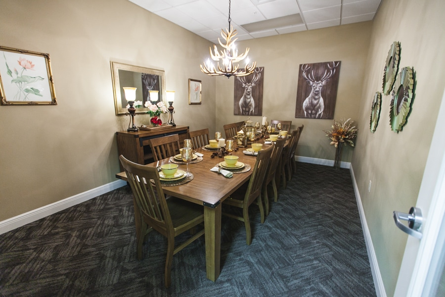 Lodge-style decorated dining room with wooden table set for ten, blue and black carpeting and decoration throughout.