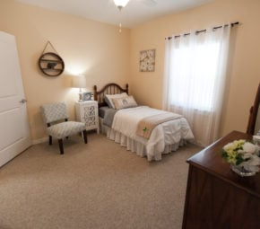 Bedroom with brown carpeting, decorated wooden dresser, and wooden mirror in the foreground, gray chair next to gray and white bed in the background.