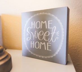 "Square decoration reading ""home sweet home"" sitting atop a cream-colored table at one of our assisted living facilities."
