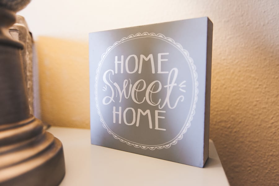 """Square decoration reading """"home sweet home"""" sitting atop a cream-colored table at one of our assisted living facilities."""