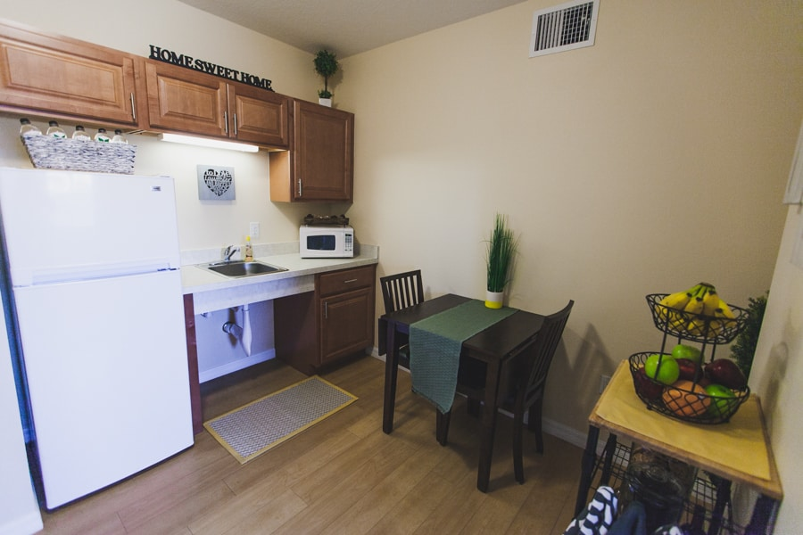 Model kitchen area with wood flooring, a small, black dining table with two black chairs, a refrigerator, and countertop.