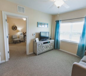 Model living room at our Land O' Lakes ALF with cream walls, gray carpeting, loveseat, and television stand, blue drapes on the wall, with a doorway leading to a bedroom in the background.