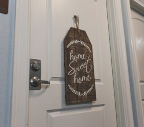 "Wooden decoration reading ""home sweet home"" in cursive font on the front of a bedroom door at one of our assisted living facilities."