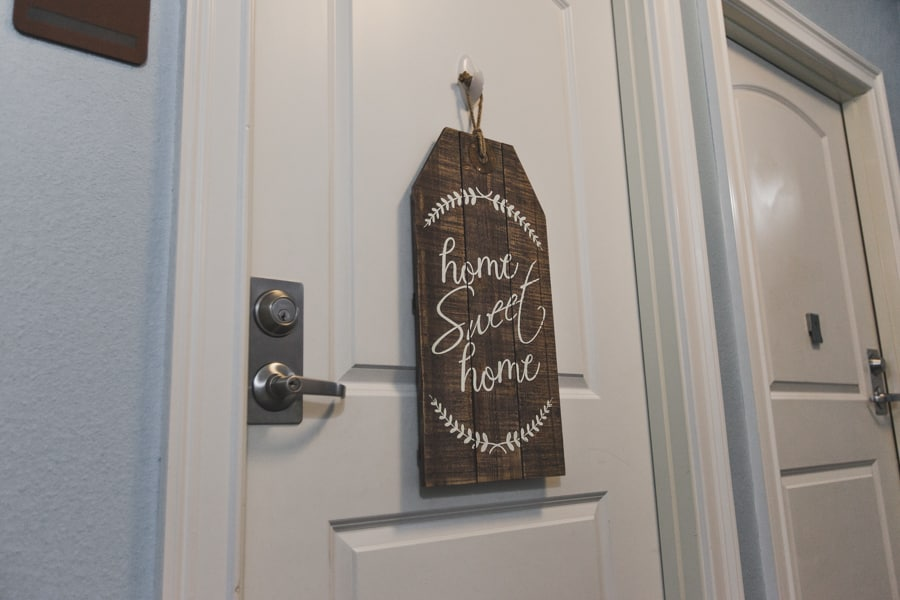 """Wooden decoration reading """"home sweet home"""" in cursive font on the front of a bedroom door at one of our assisted living facilities."""