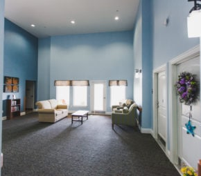 Sitting area with gray carpet and blue walls, including cream love seat and striped green and blue plush lounge chairs.