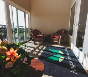 Second story porch with metal balcony and sliding glass windows, two wicker chairs with red cushions, an Angels Senior Living carpet, and floral arrangement in the foreground.