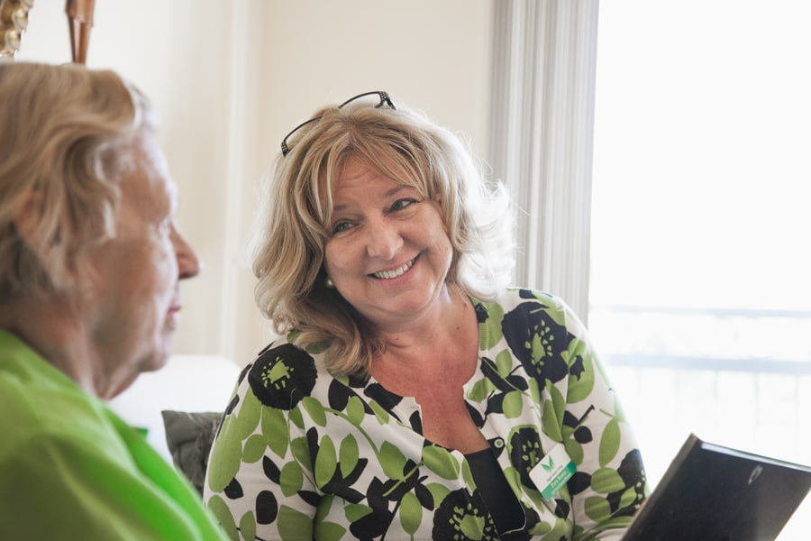 Employee in green shirt talking with resident in green shirt at our assisted living and memory care facility in Land O' Lakes, Florida.