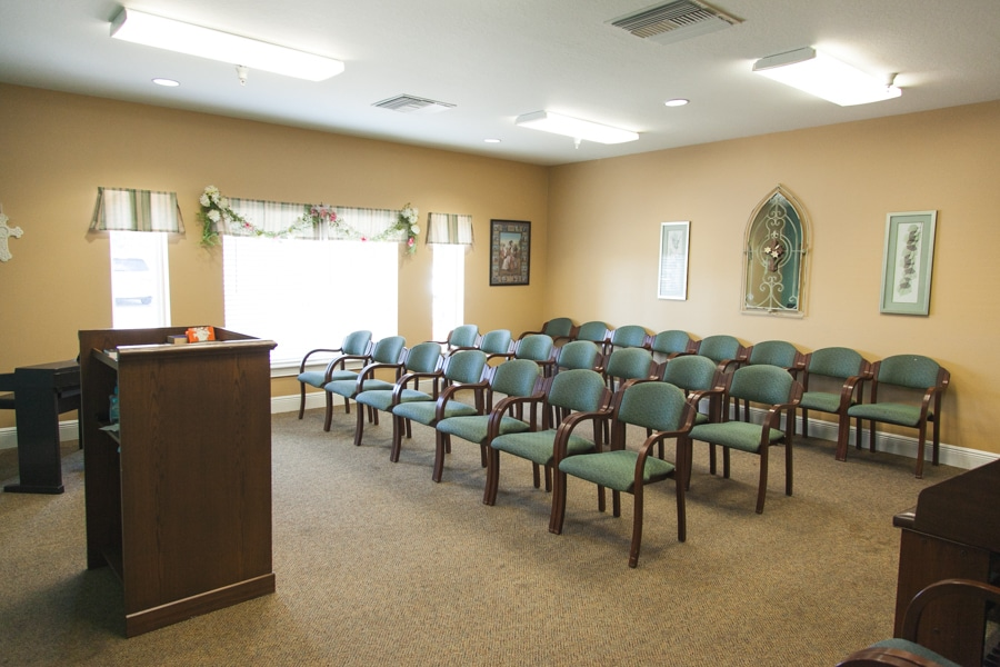 Brown carpeted chapel room with brown wooden lectern at front of room and three rows of brown wooden chairs with green cushions.