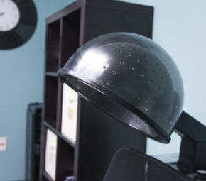 Black salon dryer located in our ALF's on-site beauty parlor, with black bookcase and analog clock in the background.