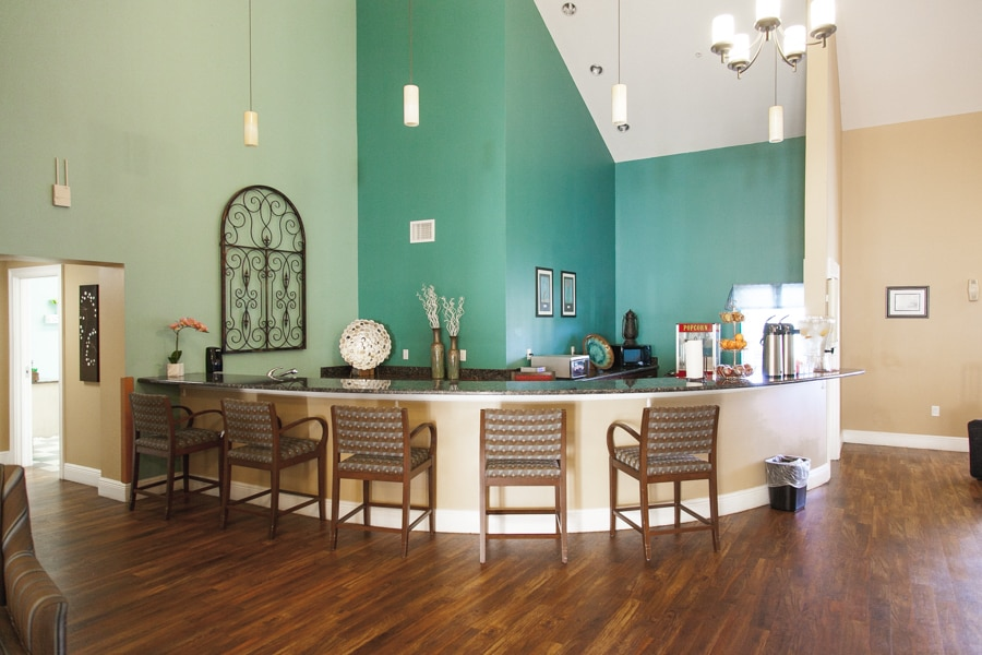 Wraparound granite countertop bar with five wooden high chairs, with blue and brown walls and snacks in the background.