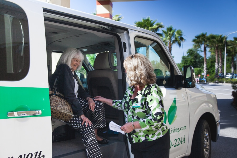 A resident gets help from an employee disembarking a company vehicle at our assisted living facility in Land O' Lakes, Florida.