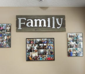 "A brown wall with mounted wooden board reading ""Family"" in metal letters, with three collages of residents."