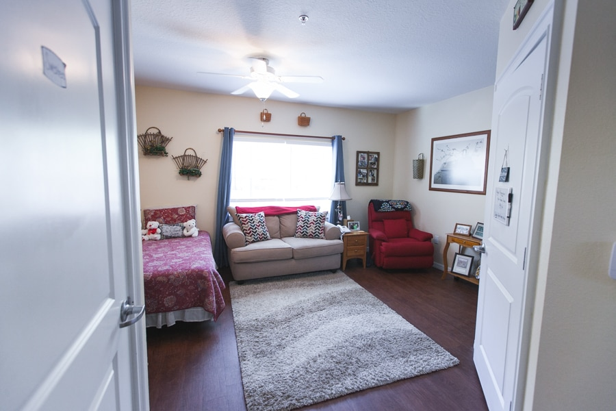 Model bedroom with wood flooring, gray carpet, gray loveseat, red chair, wooden furniture, and bed with red paisley sheet against a decorated wall.