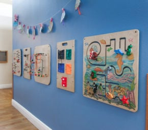 Interactive games mounted on wooden platforms on a blue wall.