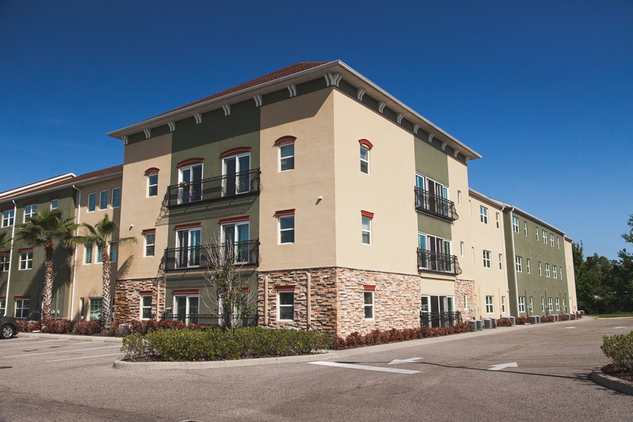 Exterior of assisted living and memory care facility in Land O' Lakes, Florida featuring first floor pavers and alternating sand and olive paint.