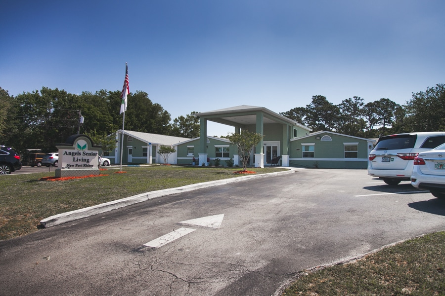 Parking lot and sign of New Port Richey ALF in foreground, olive-colored facility with white accenting on windows, doors, roofs, and pedestals in background.