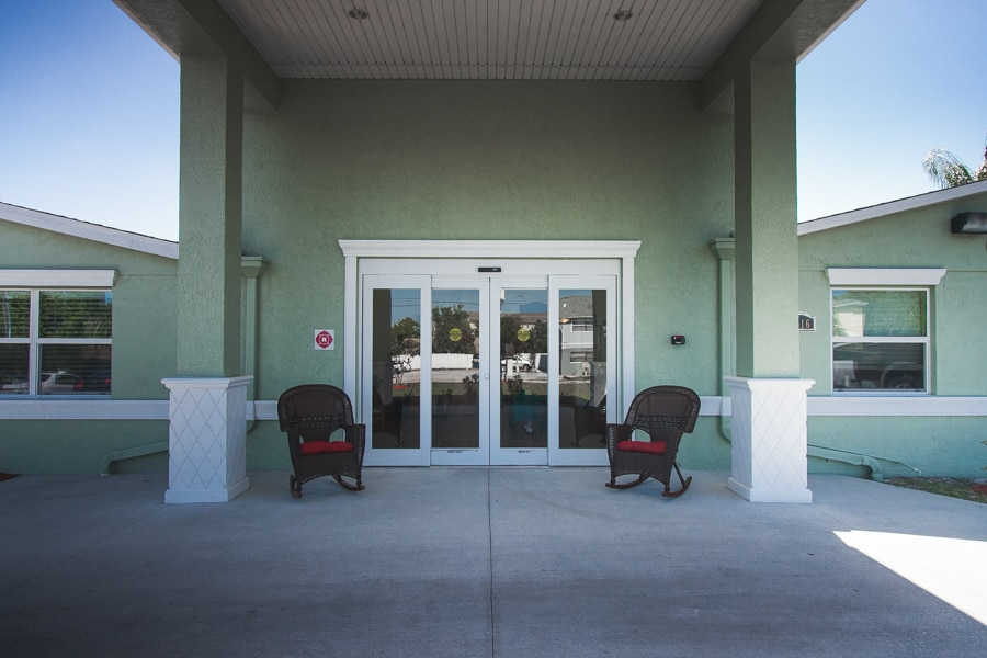 Olive-colored entryway to New Port Richey assisted living facility, including two high columns with white pedestals and automatic door.