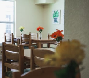 Dining room featuring orange and yellow floral centerpieces on wooden tables with four brown wooden chairs, window in the background.