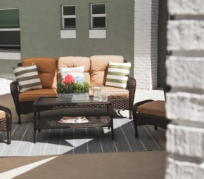 Outdoor lounge area with brown wicker couch, coffee table, and chairs, orange cushions, and decorative pillows.