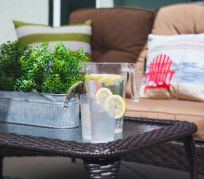 Tin can of greenery with two glasses and a pitcher of water with lemon on a brown wicker table, with a brown couch and decorative pillows in the background.