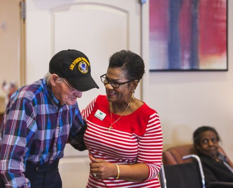 Angels Senior Living employee helps a veteran resident walk around.