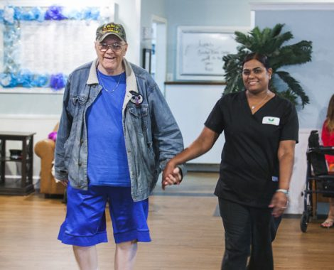 angels senior living employee holding hand of old resident and walking