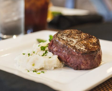 A white plate with steak and mashed potatoes sitting atop it as an example of cuisine available at our assisted living facility in Lutz, Florida.