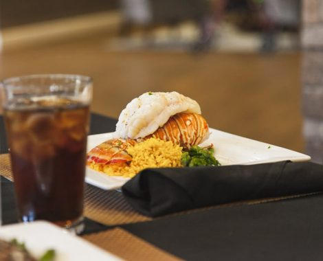A lobster tail with rice and vegetables sitting on a white plate next to a rolled black napkin.