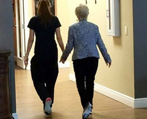 assisted living employee and resident walking together